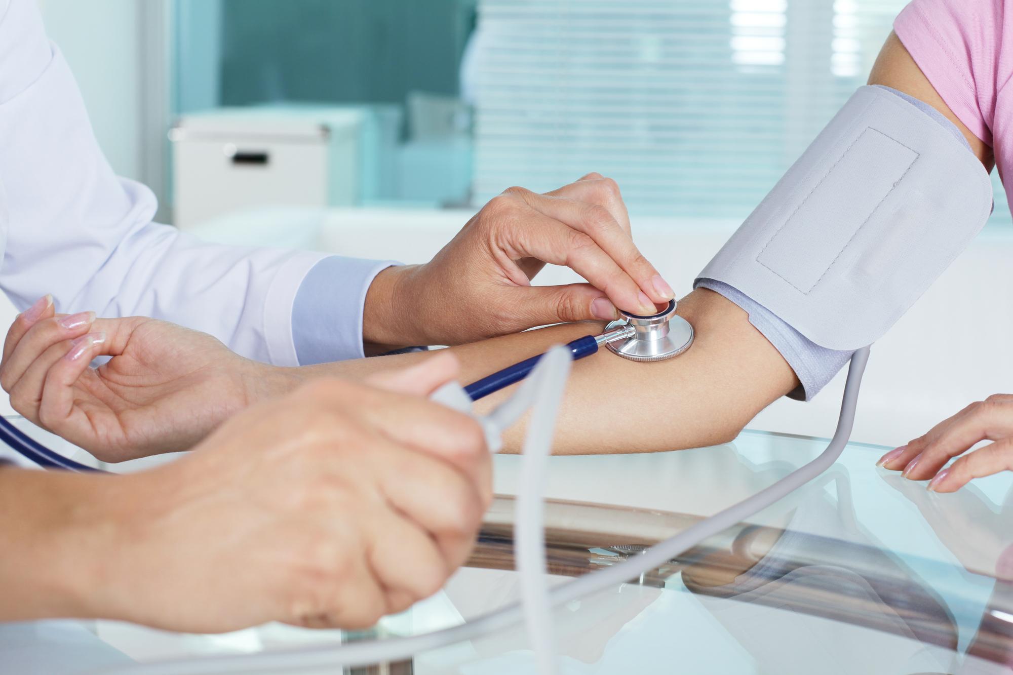 Médico tomando tensión paciente en consulta
