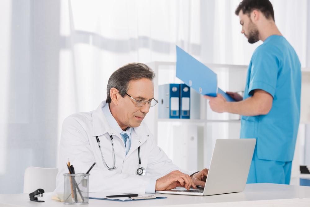 Médico escribiendo en un ordenador. Asistencia telemática